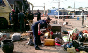 A security officer examines abandoned items at the scene of a blast in the northern Nigerian city of Kano, Photo: AFP